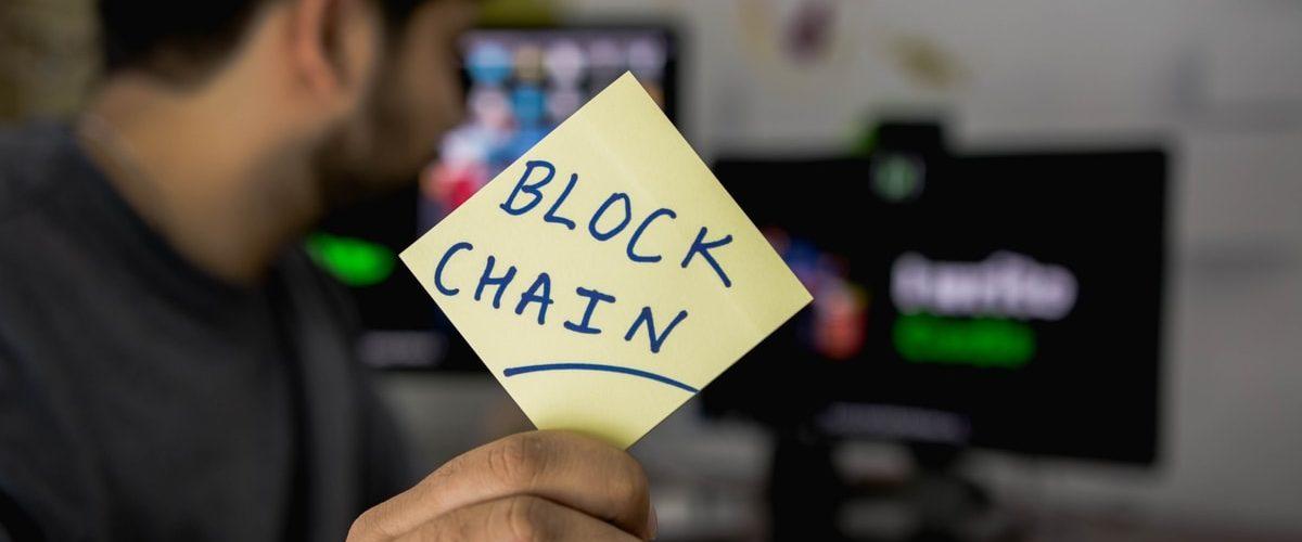 """homme avec post-in écrit """"blockchain"""""""